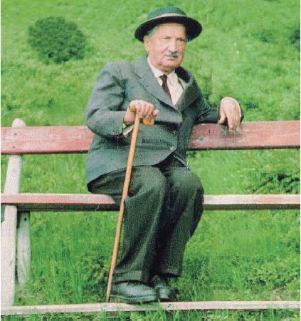 Heidegger in grüner Jägerjoppe und Spazierstock auf einer Bank. Schaut nachdenklich nach vorne.