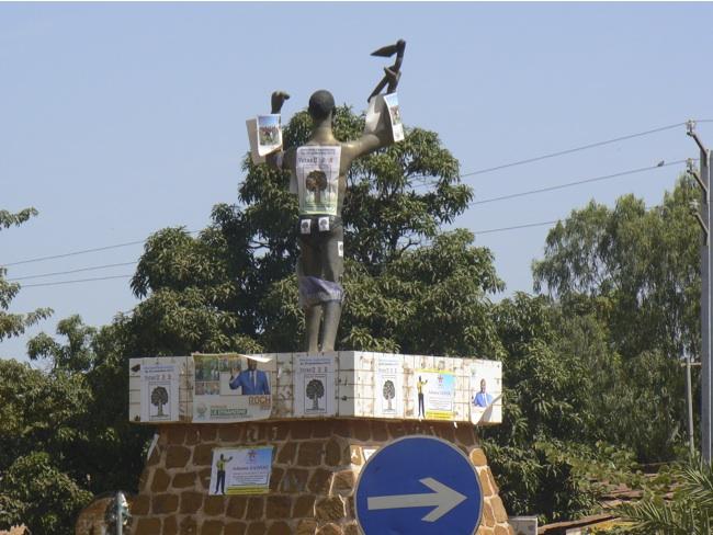 Manifesti elettorali su una statua del centro di Bobo-Diulasso